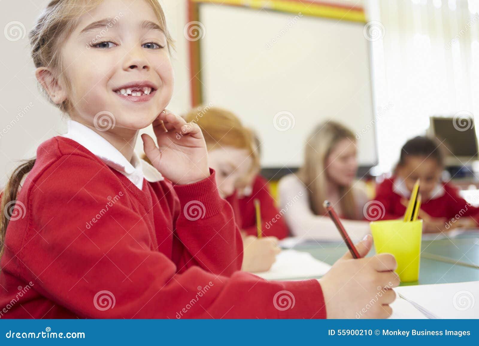 Kvinnlig elementär elev som arbetar på skrivbordet