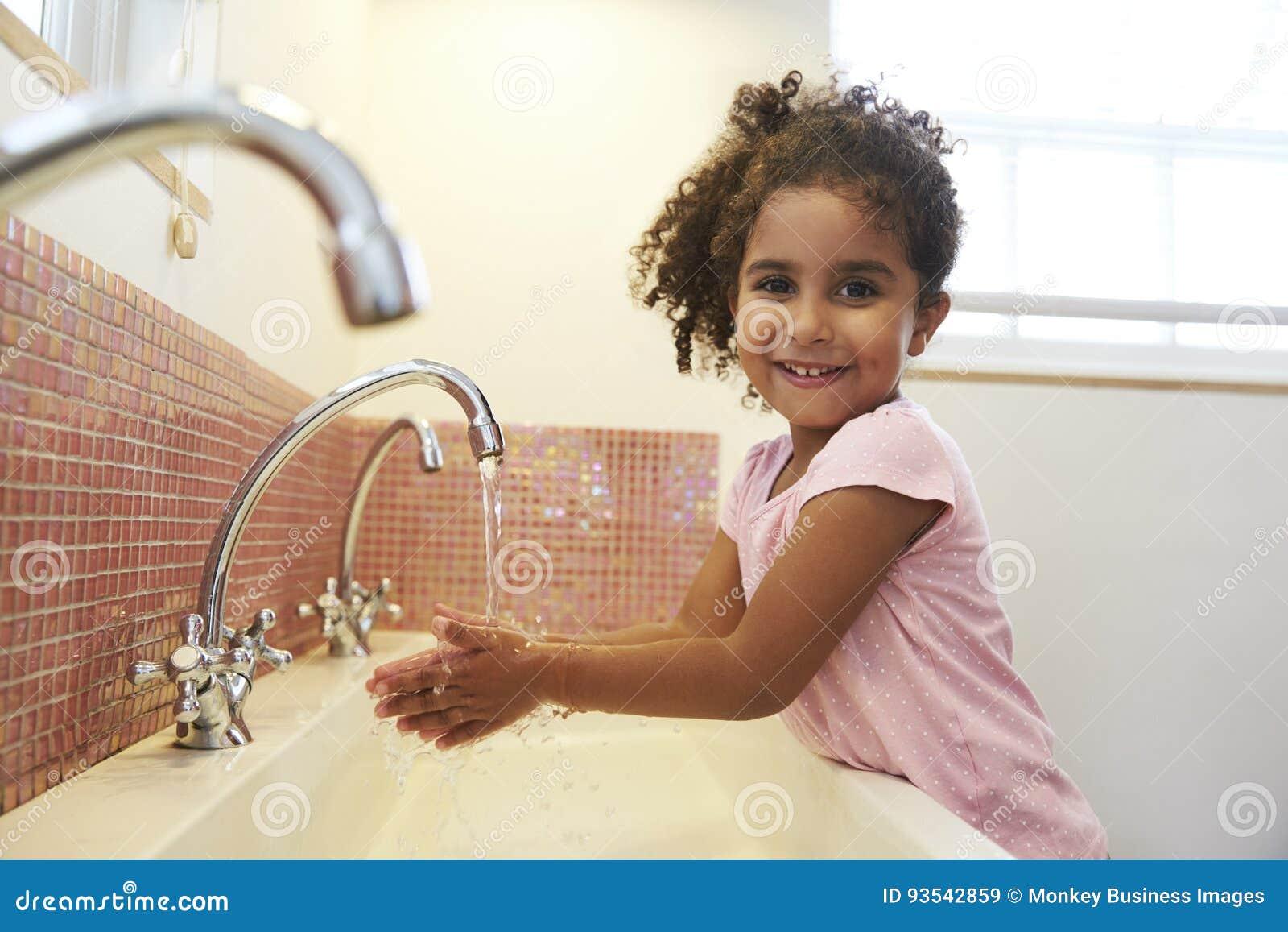 Kvinnlig elev på händer för Montessori skolatvagning i toalett
