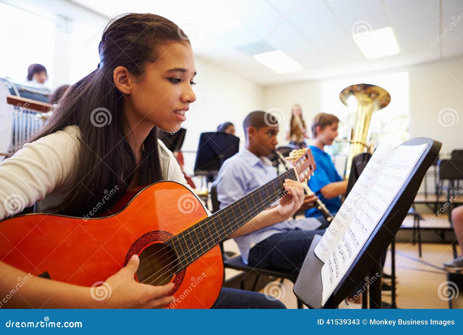 Kvinnlig elev som spelar gitarren i högstadiumorkester
