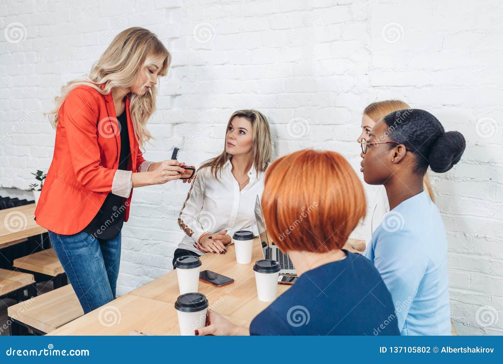 Kvinnlig försäljningskonsulent som berättar om nytt gods till unga affärskvinnor