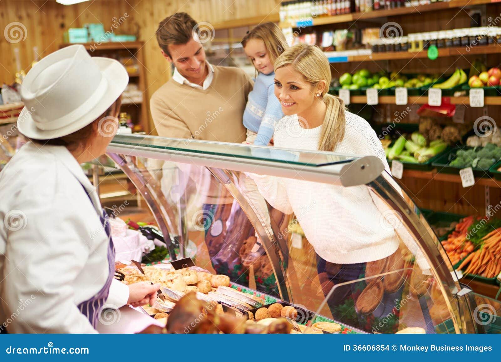 Kvinnlig familj för försäljningsassistentportion i matvaruaffär
