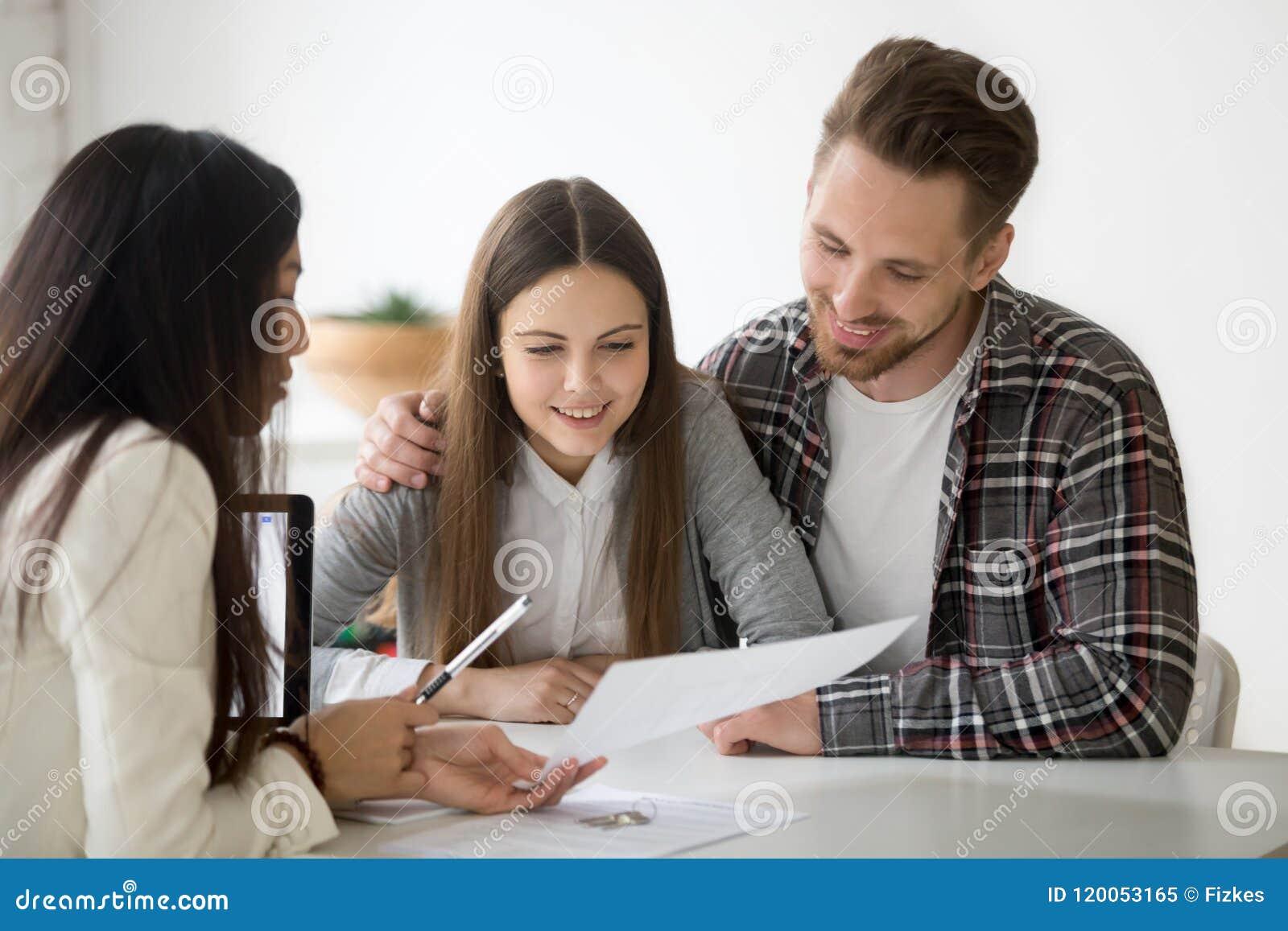 Kvinnlig fastighetsmäklare som konsulterar den millennial maken på att köpa för egenskap