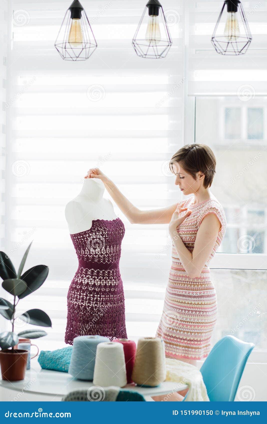 Kvinnlig formgivare som arbetar med den stack klänningen i den hemtrevliga studioinre, frilans- livsstil Skjuten lodlinje
