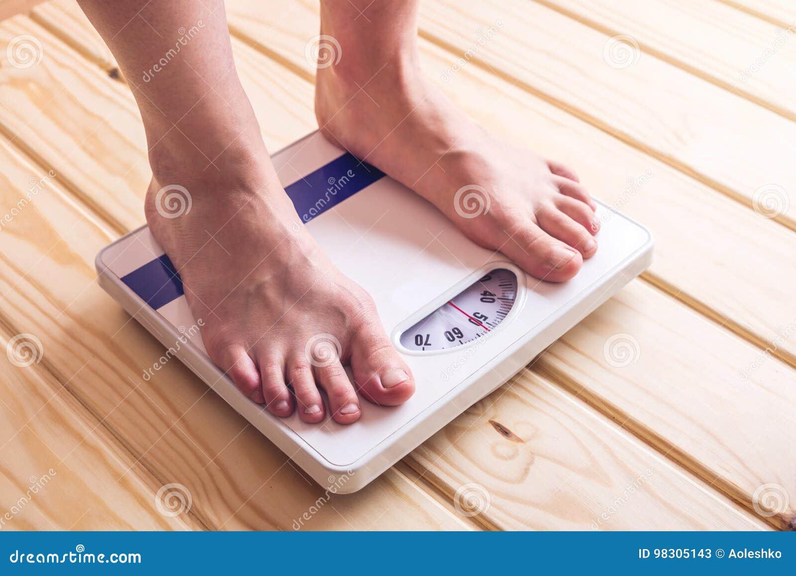 Kvinnlig fot som står på mekanisk våg för viktkontroll på träbakgrund Begrepp av bantning- och viktförlust