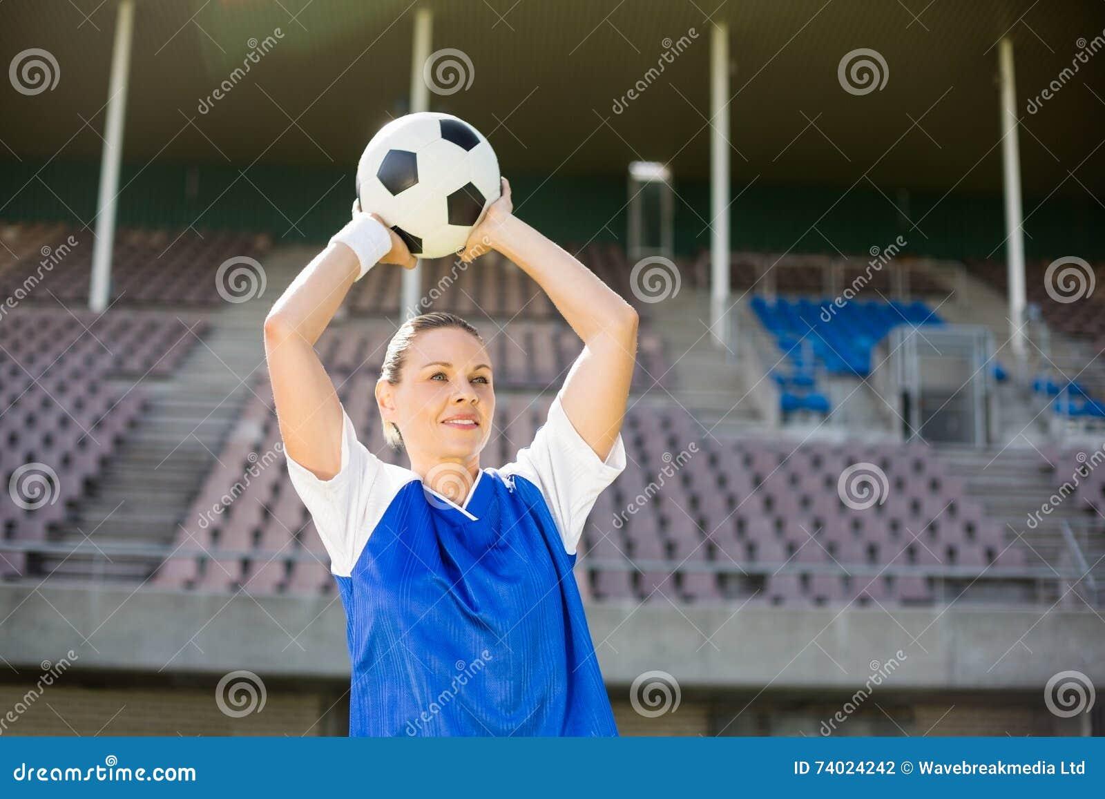 Kvinnlig fotbollsspelare omkring som kastar en fotboll