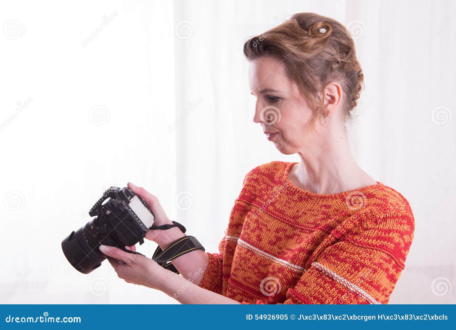 Kvinnlig fotograf på arbete med kameran