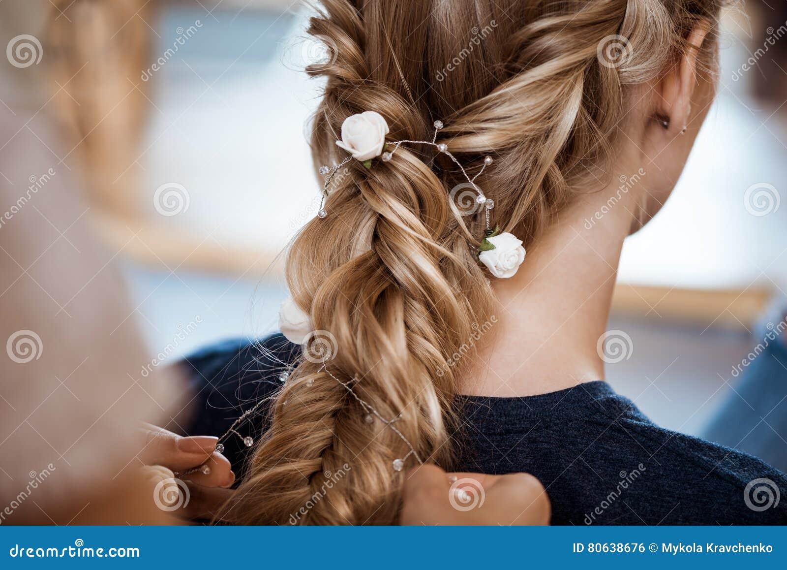 Kvinnlig frisördanandefrisyr till den blonda flickan i skönhetsalong