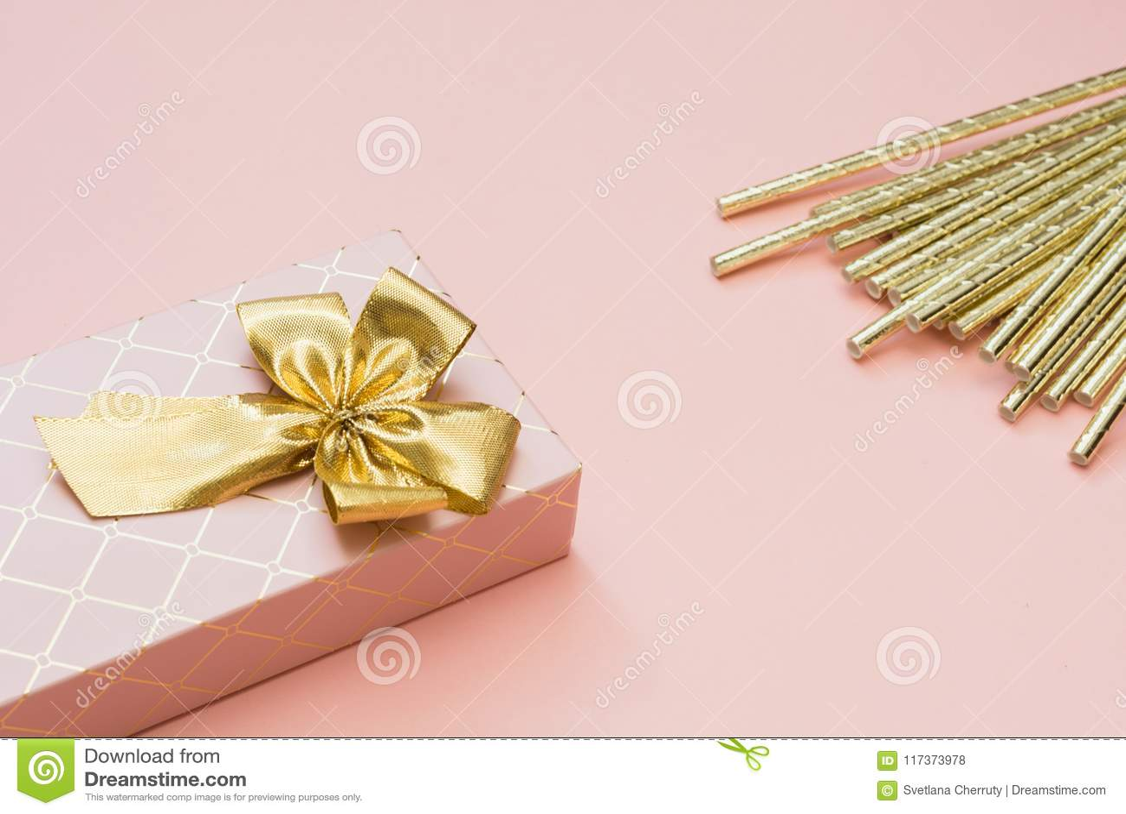 Kvinnlig gåvaask med guld- band- och coctailtillbehör på punchy pastellfärgade rosa färger kopiera avstånd