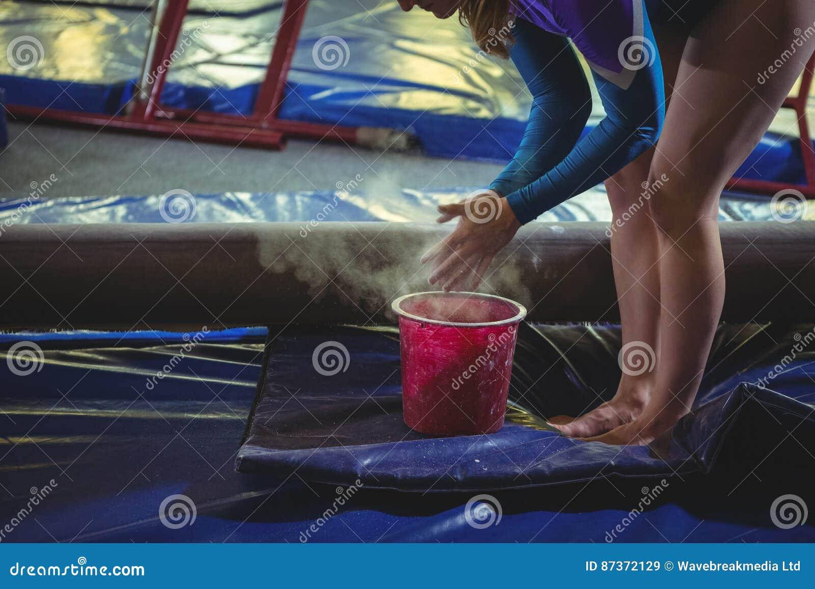 Kvinnlig gymnast som applicerar kritapulver på hennes händer, innan övning