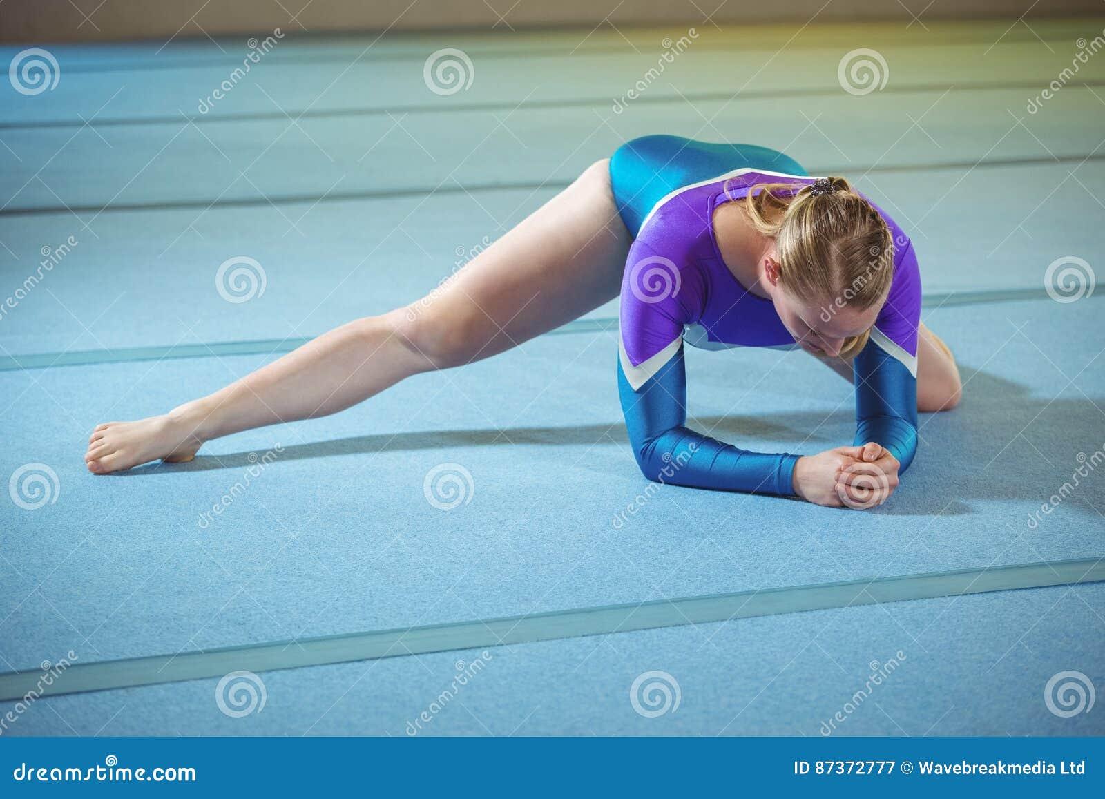 Kvinnlig gymnast som utför sträcka övning