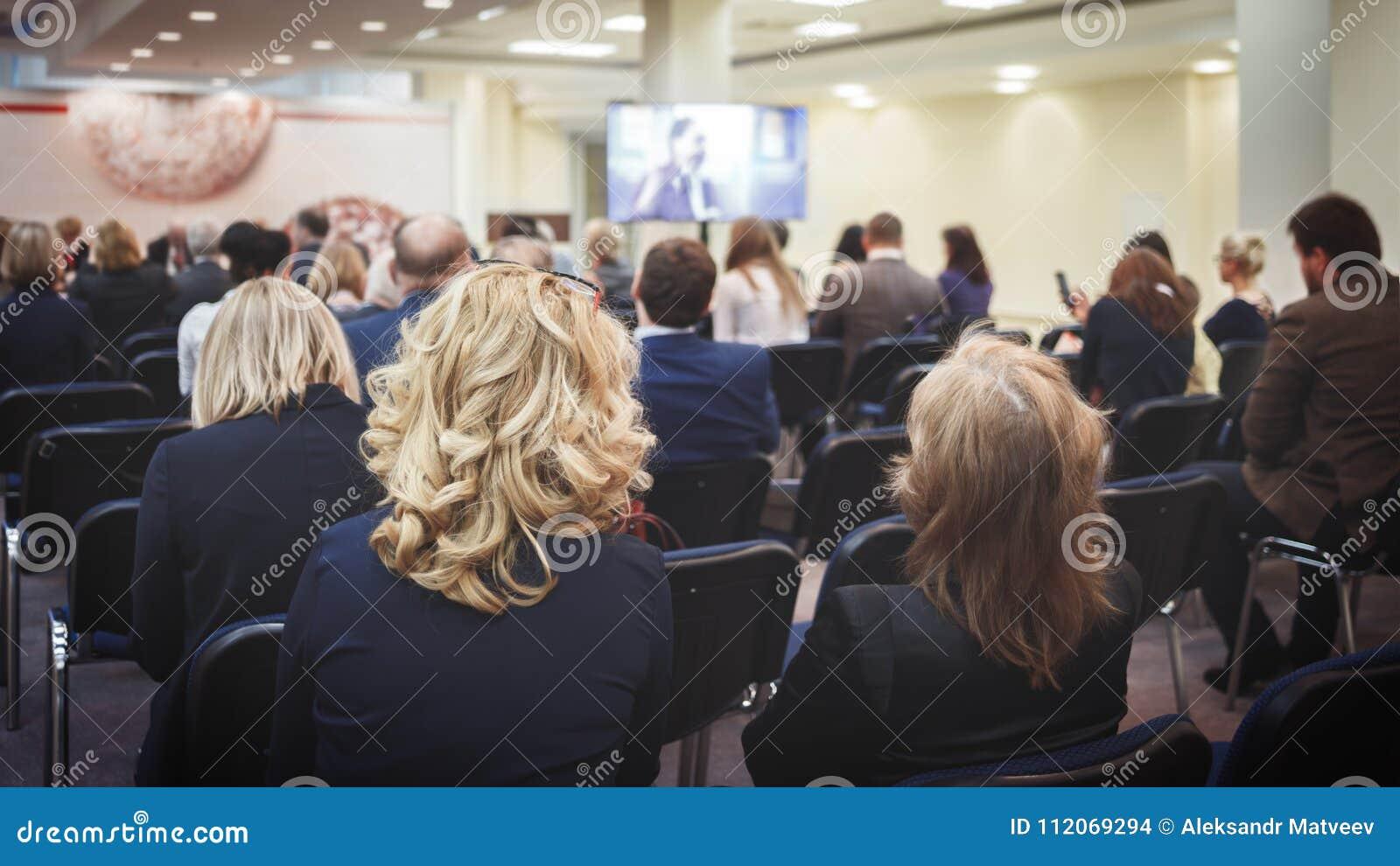 Kvinnlig högtalare som ger presentation i hörsal på universitetseminariet Bakre sikt av oigenkännliga deltagare som lyssnar till