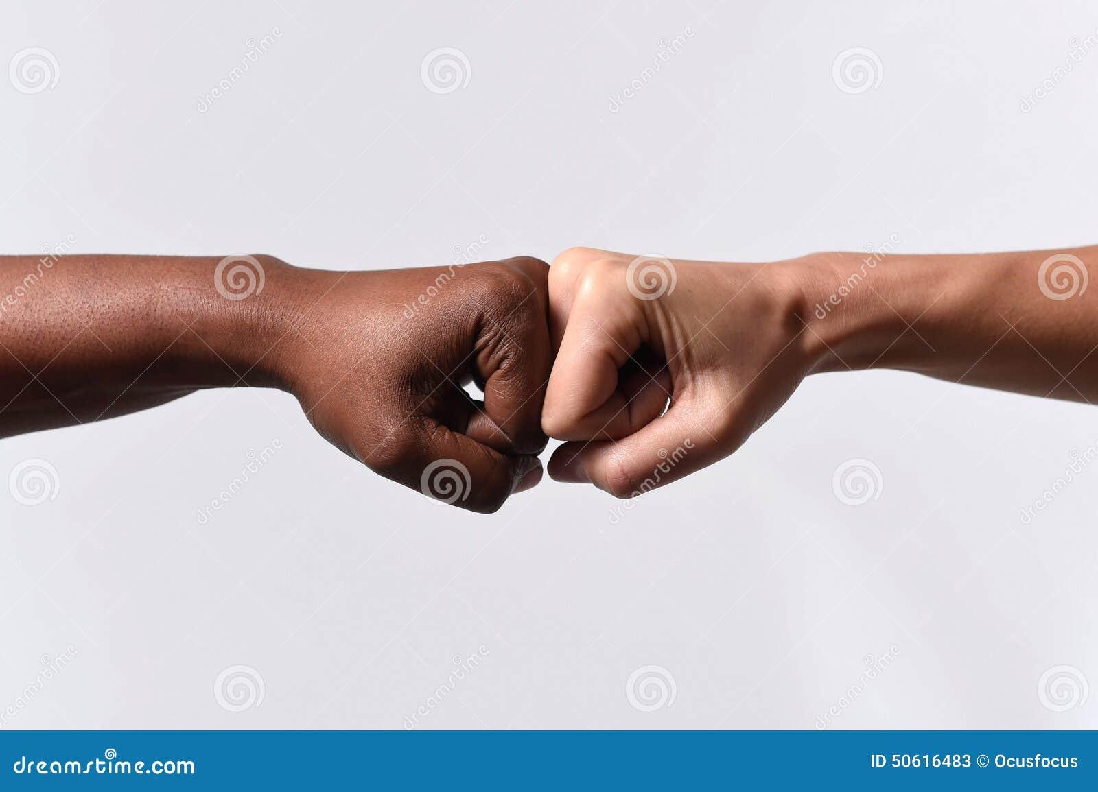 Kvinnlig hand för svart afrikansk amerikanlopp som trycker på knogar med den vita Caucasian kvinnan i blandras- mångfald