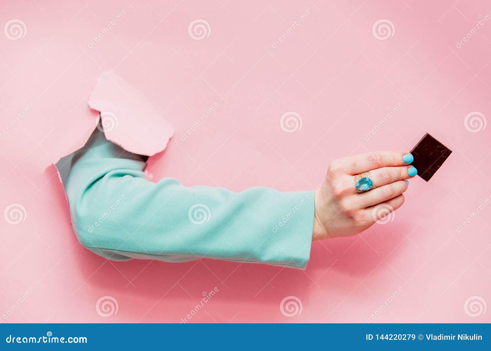 Kvinnlig hand i klassiskt blått omslag med chokladblickar