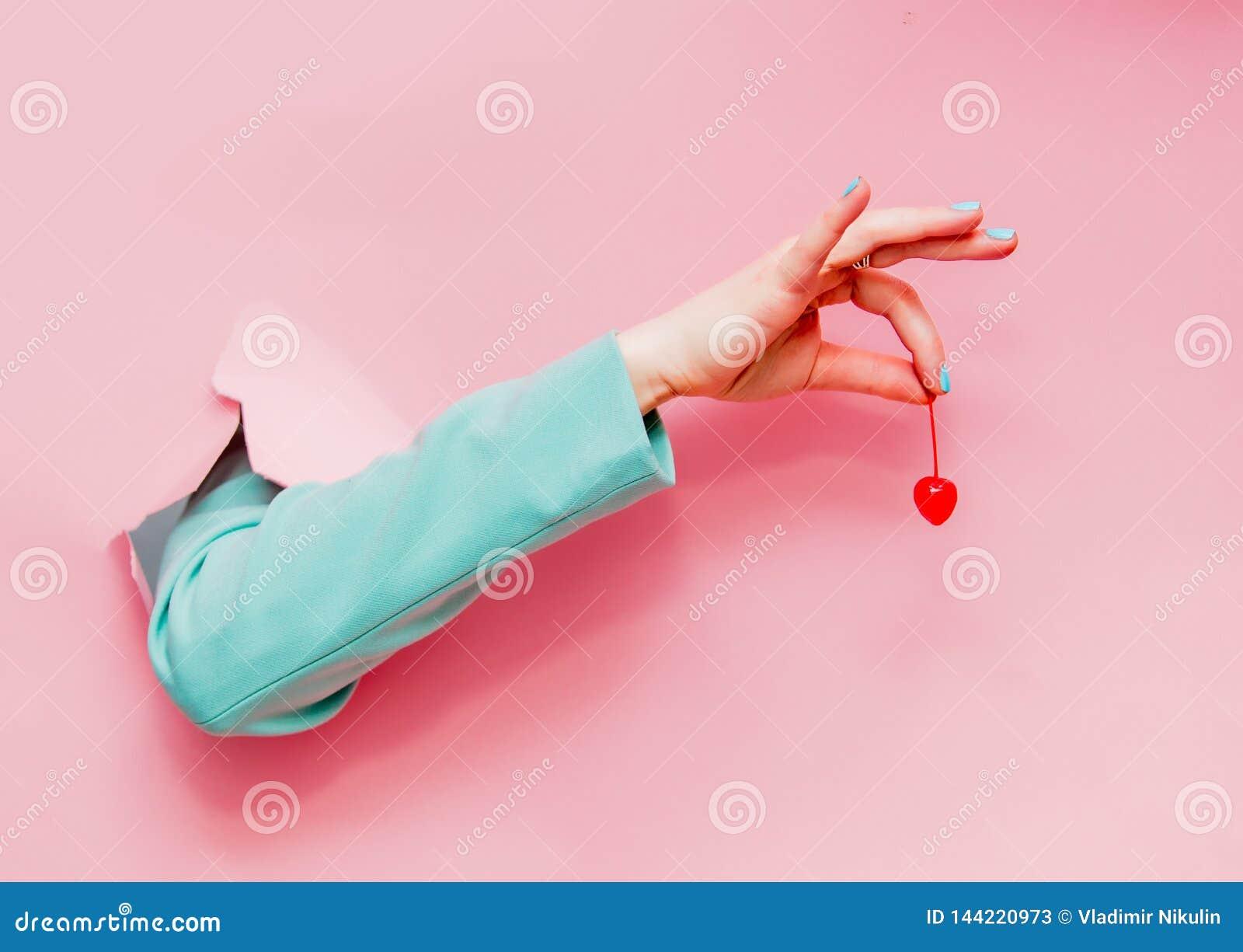 Kvinnlig hand i klassiskt blått omslag med körsbäret