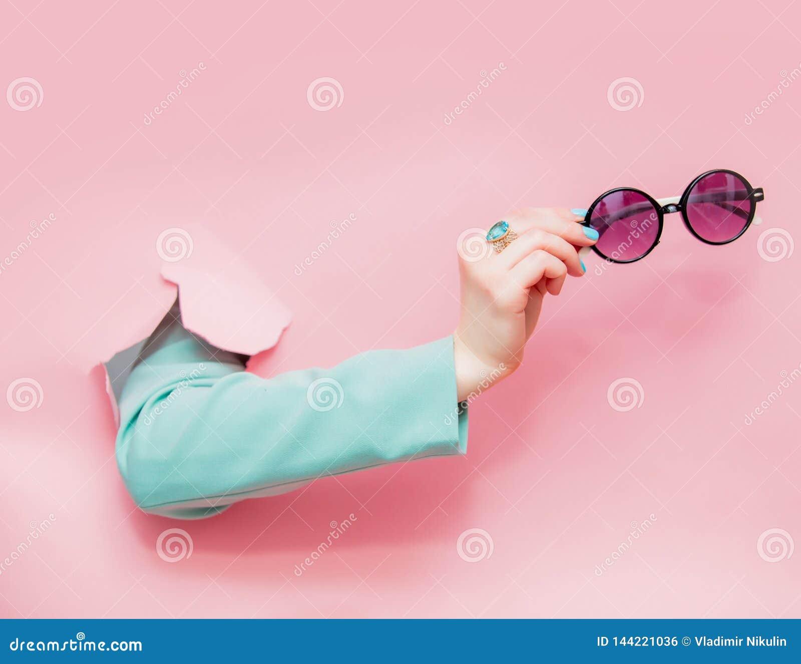 Kvinnlig hand i klassiskt blått omslag med solglasögonblickar