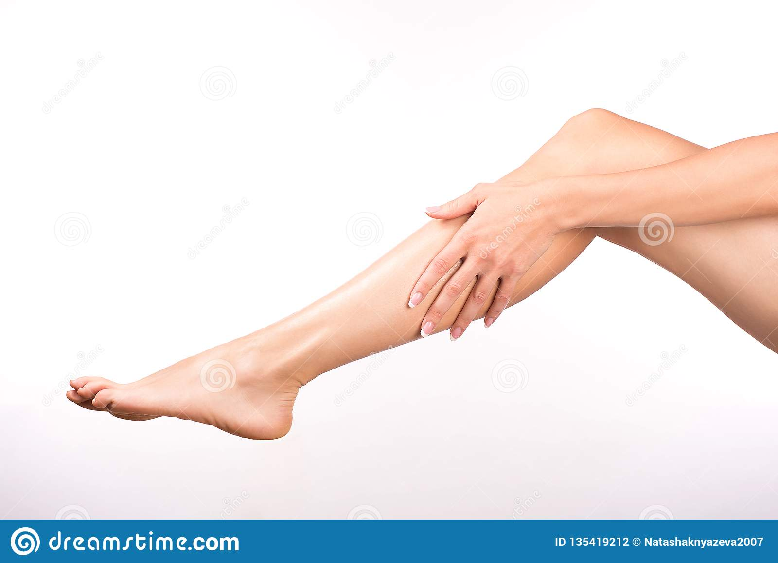 Kvinnlig hand med benet för smekning för fransk manikyr det kala, på vitt