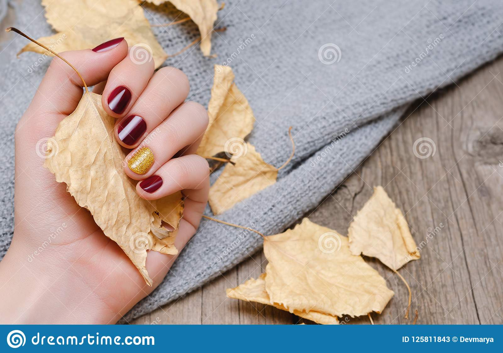 Kvinnlig hand med rött mörker - spika designen
