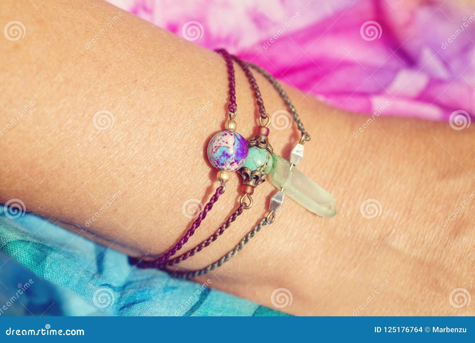 Kvinnlig hand som bär naturliga stenpärlarmband