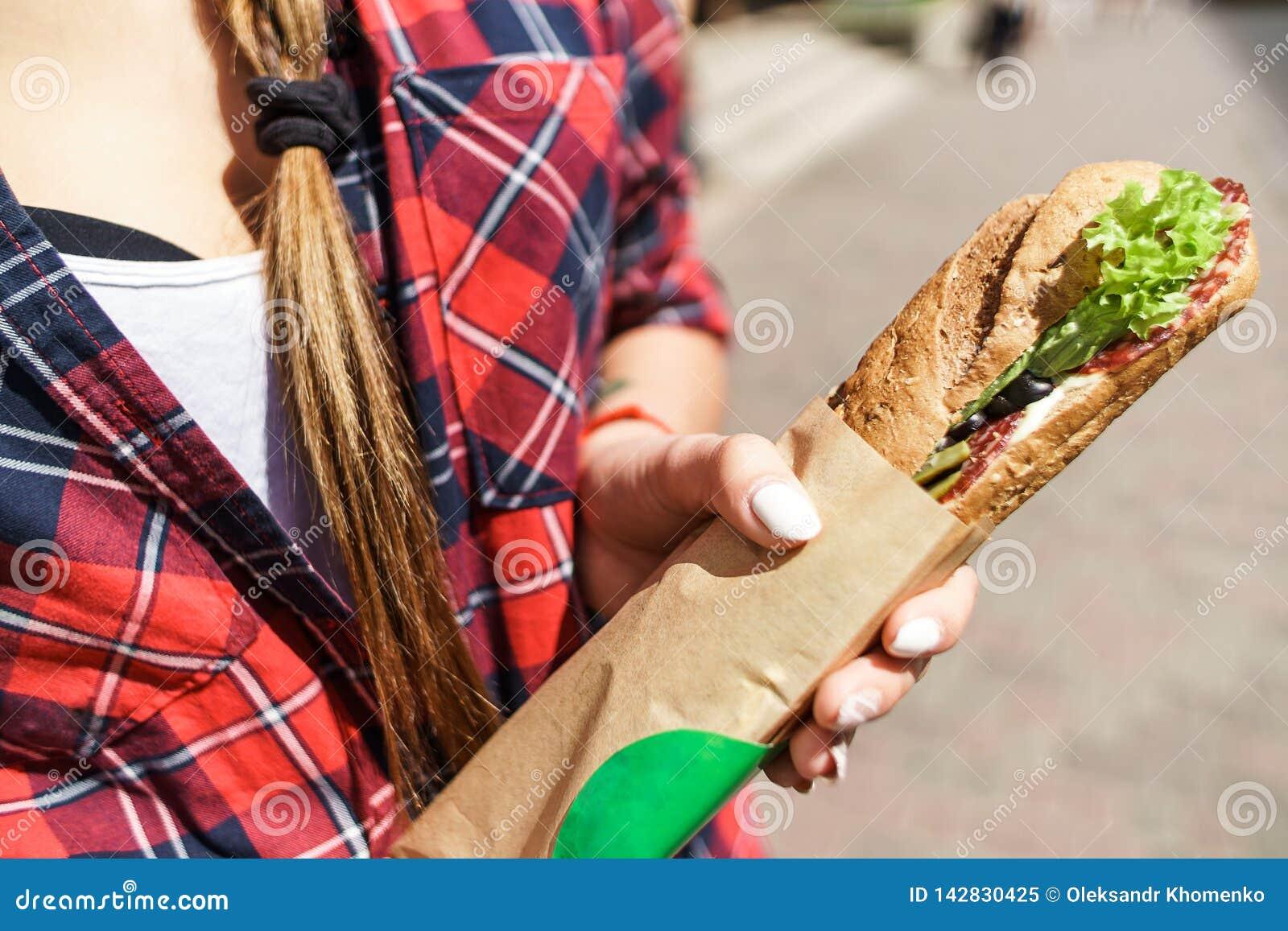 Kvinnlig hand som rymmer en smörgås