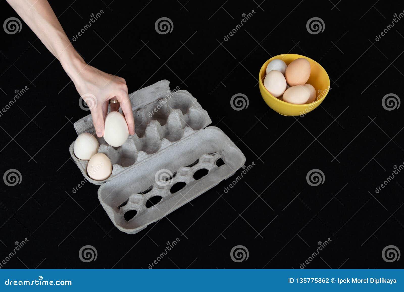Kvinnlig hand som tar ett ägg från det pappers- magasinet på svart bakgrund