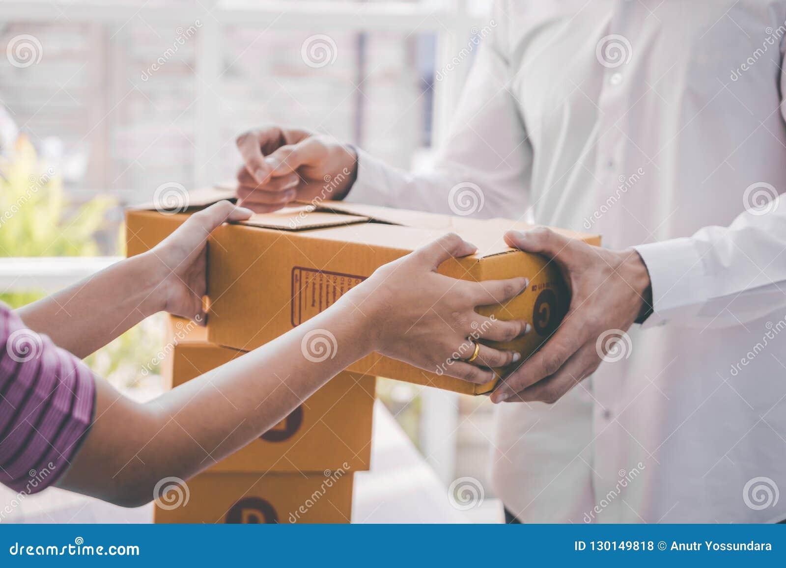 Kvinnlig hem- företagsägare som behandlar packen till kunden