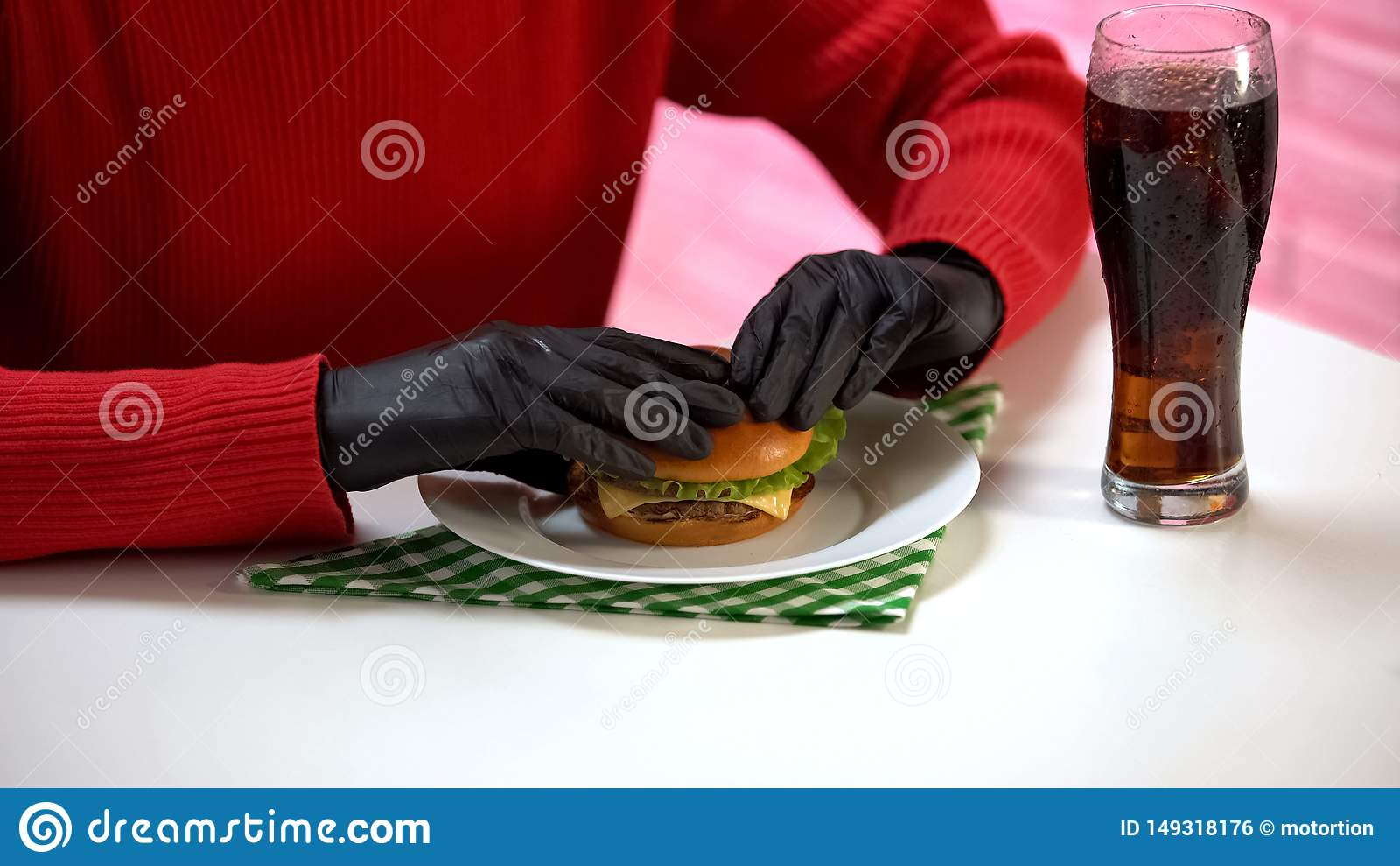 Kvinnlig i svarta gummihandskar som rymmer den smakliga hamburgaren och dricker sodavattenvatten