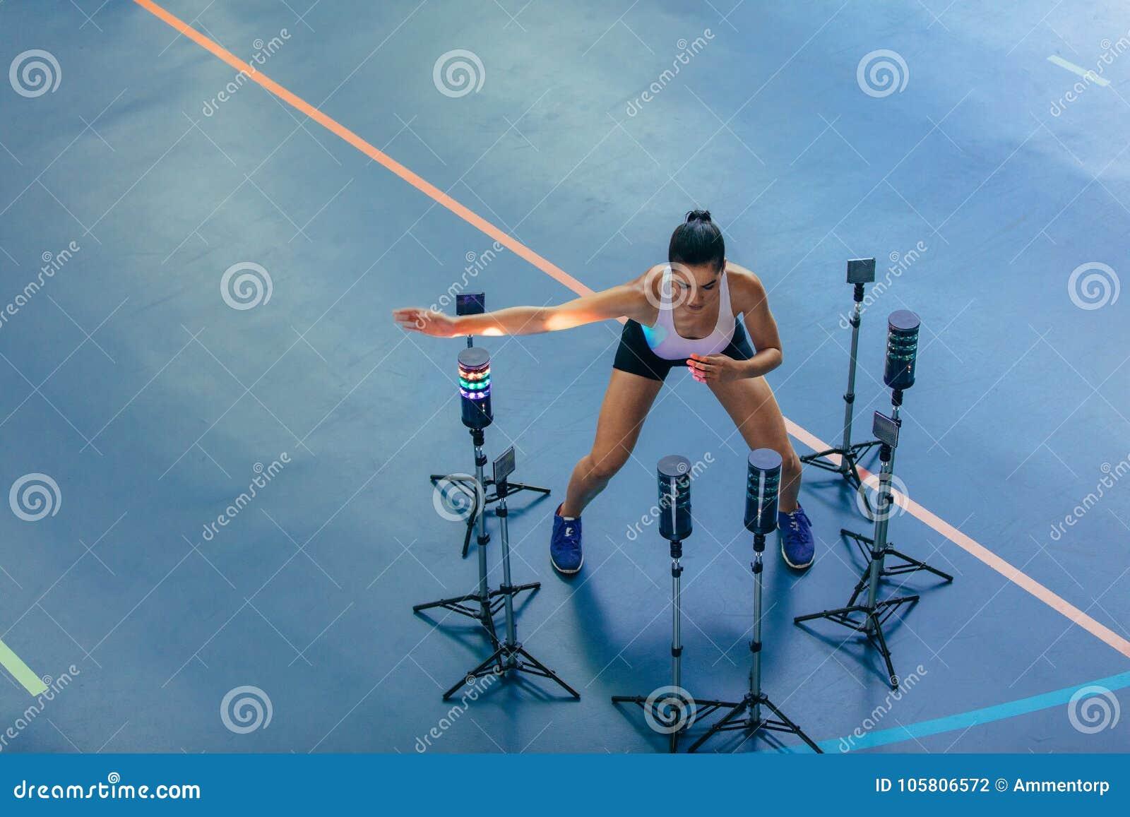 Kvinnlig idrottsman nen med det visuella stimulanssystemet på idrottshallen