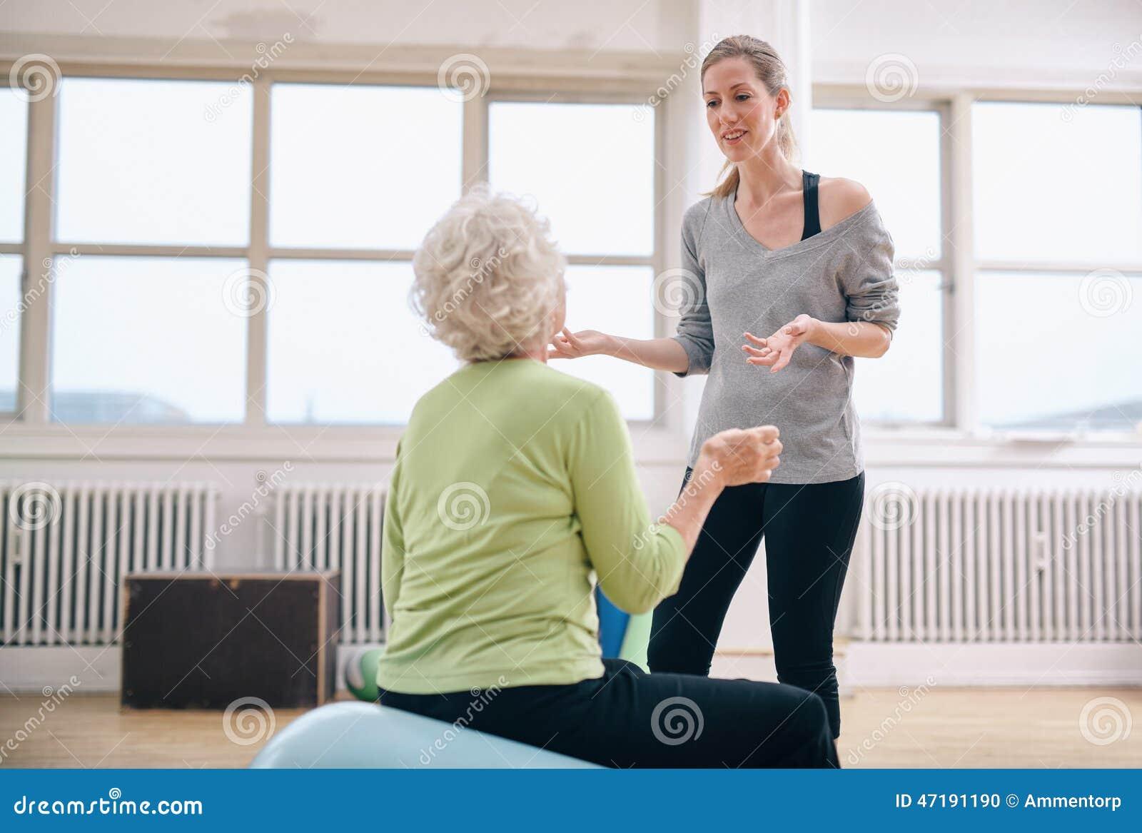 Kvinnlig instruktör som diskuterar framsteg med den äldre kvinnan
