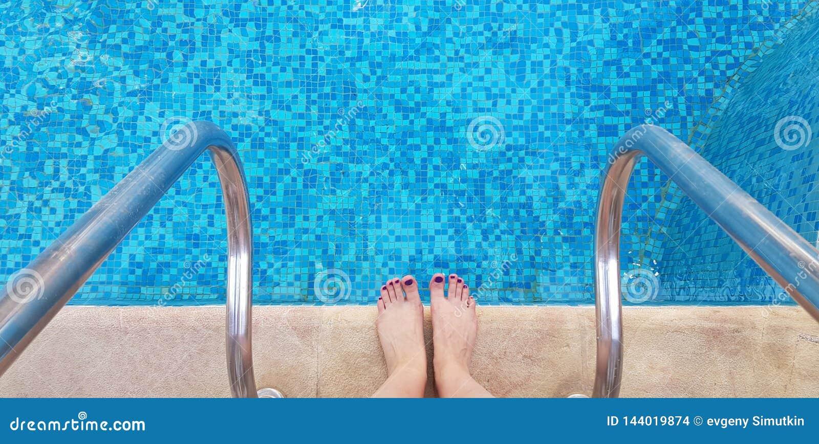 Kvinnlig kal fot som står på kanten av simbassänghalvan som är klar att skriva in