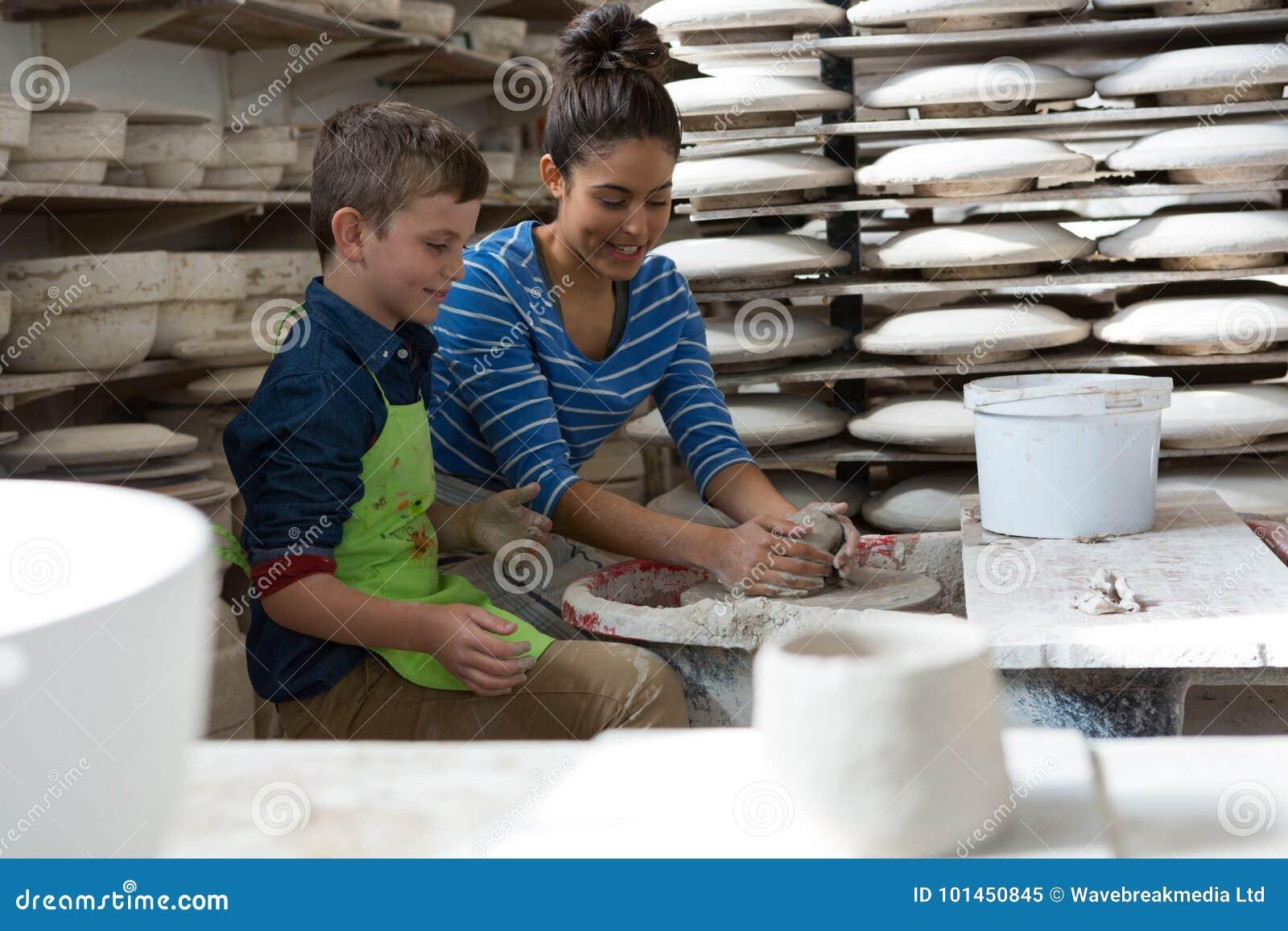 Kvinnlig keramiker som hjälper en pojke