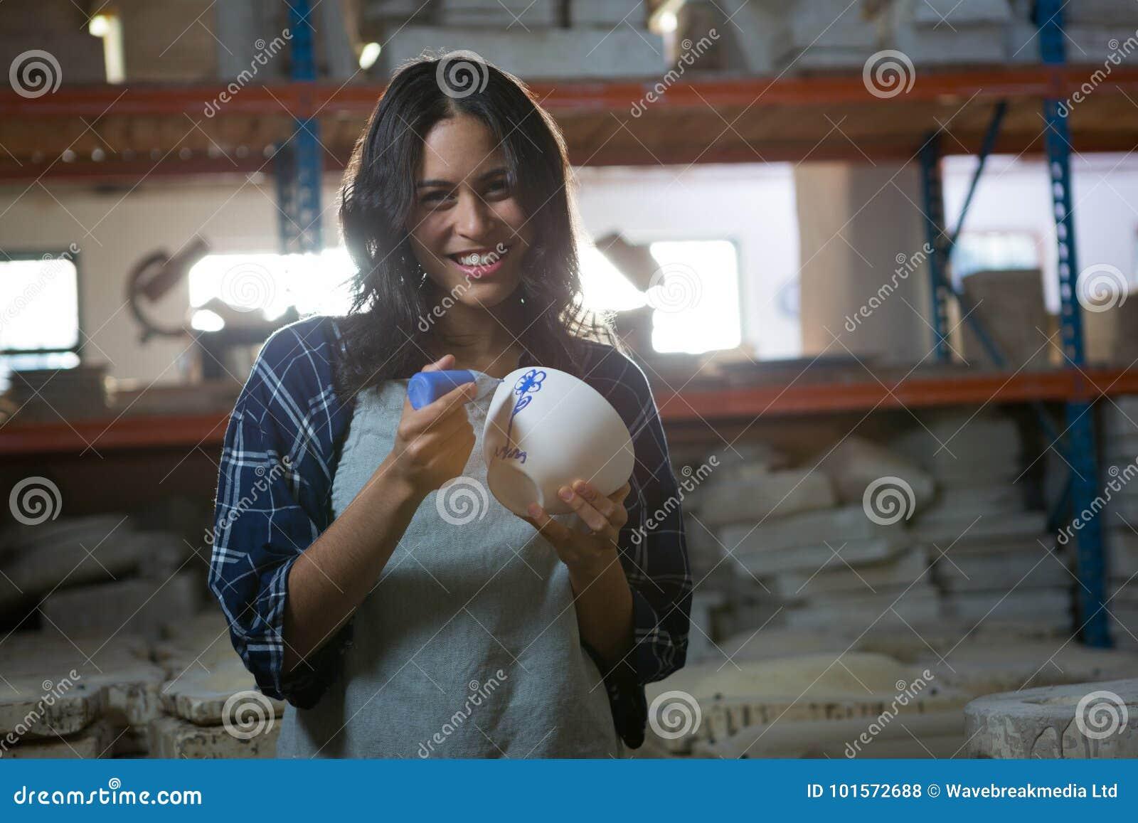 Kvinnlig keramiker som målar en bunke