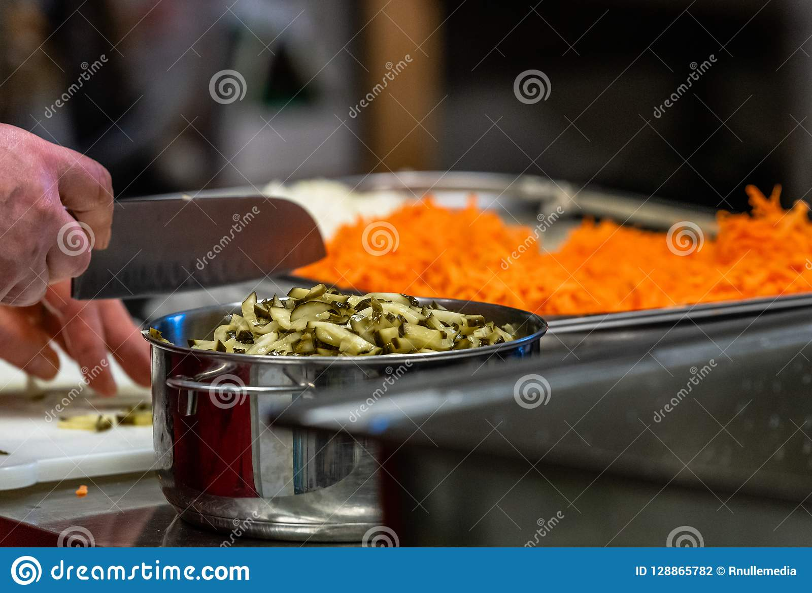 Kvinnlig kock Chopping Pickled Cucumbers för sallader som gifta sig mål