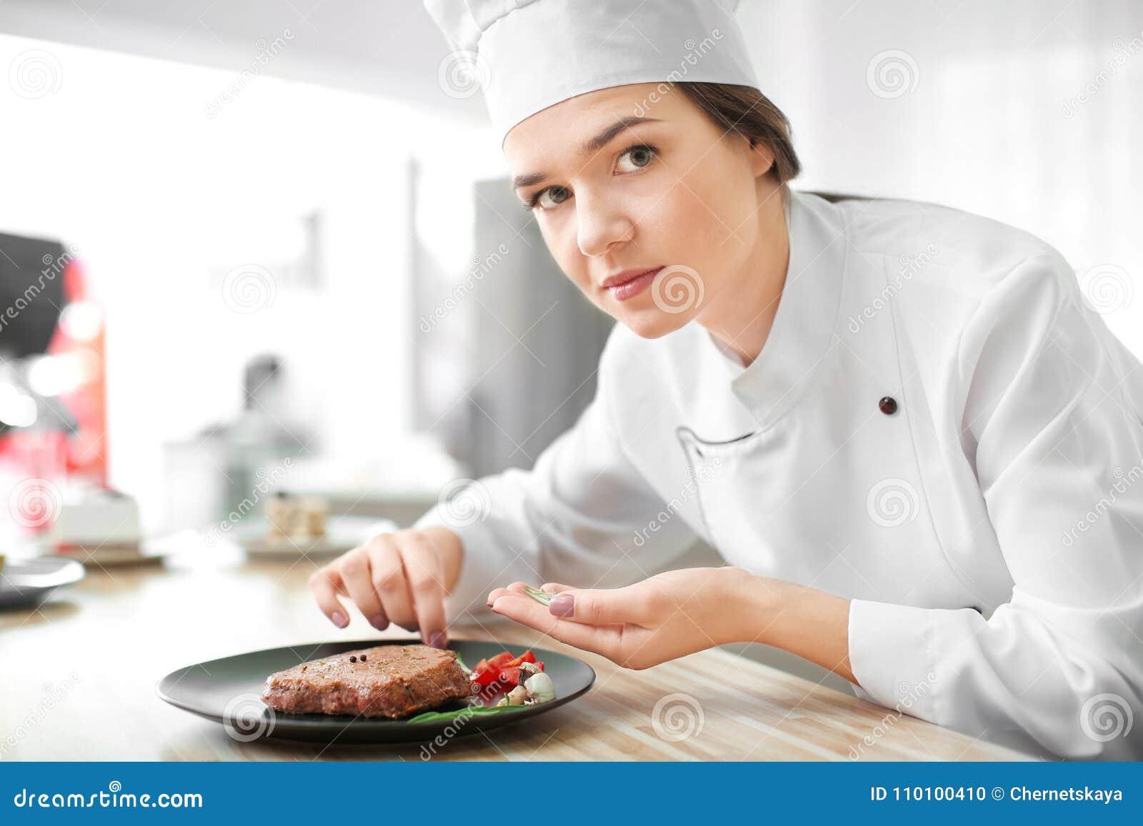 Kvinnlig kock som förbereder smaklig biff