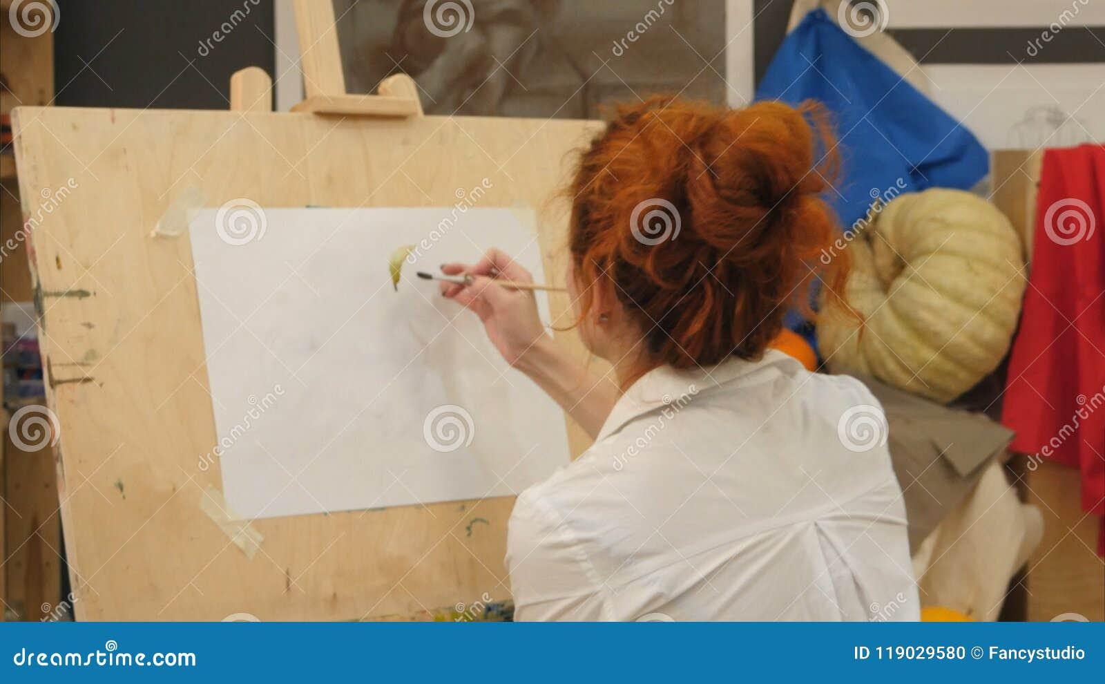 Kvinnlig konstnär som arbetar på vattenfärgmålning i studio