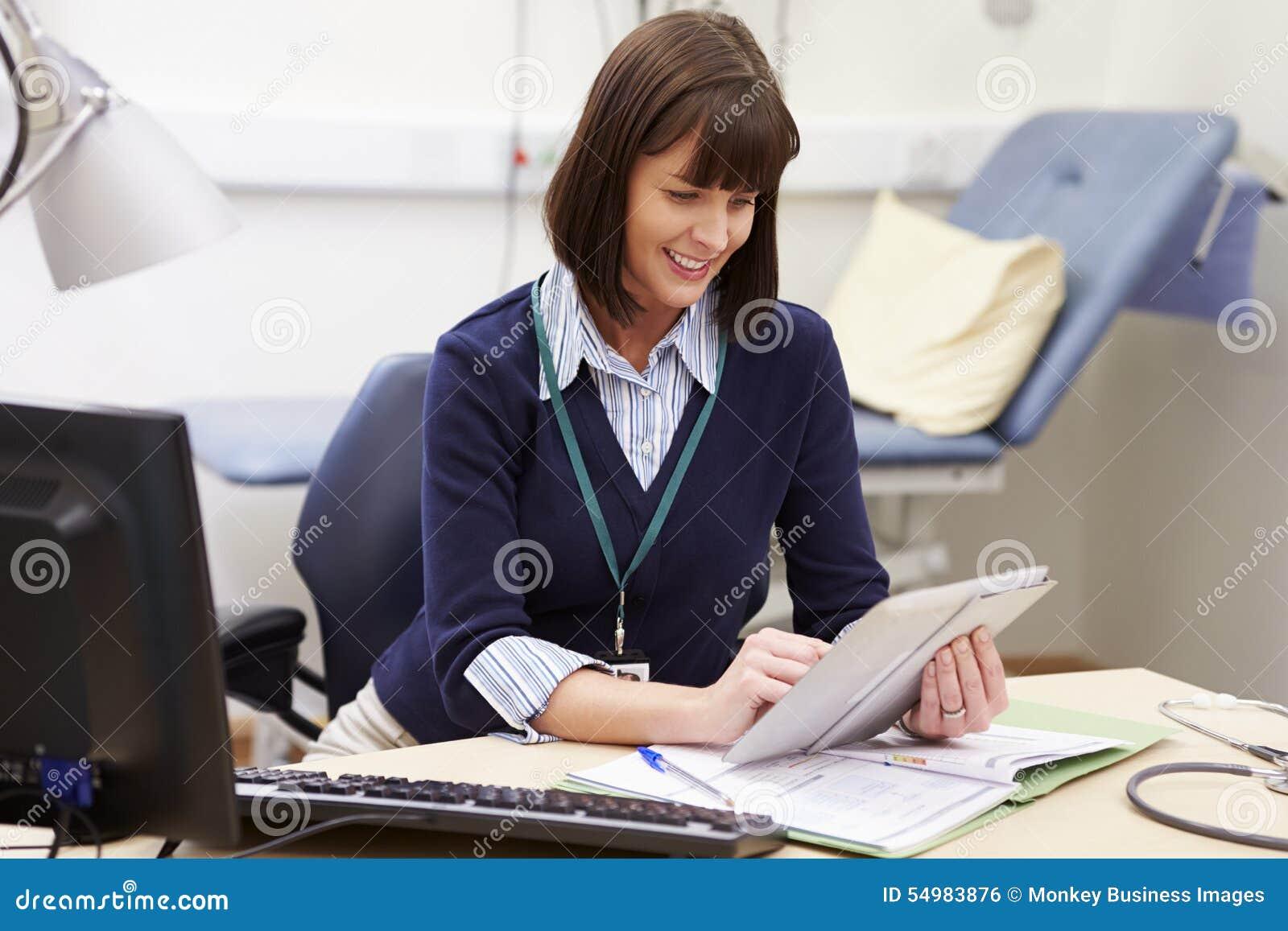 Kvinnlig konsulent Using Digital Tablet på skrivbordet i regeringsställning