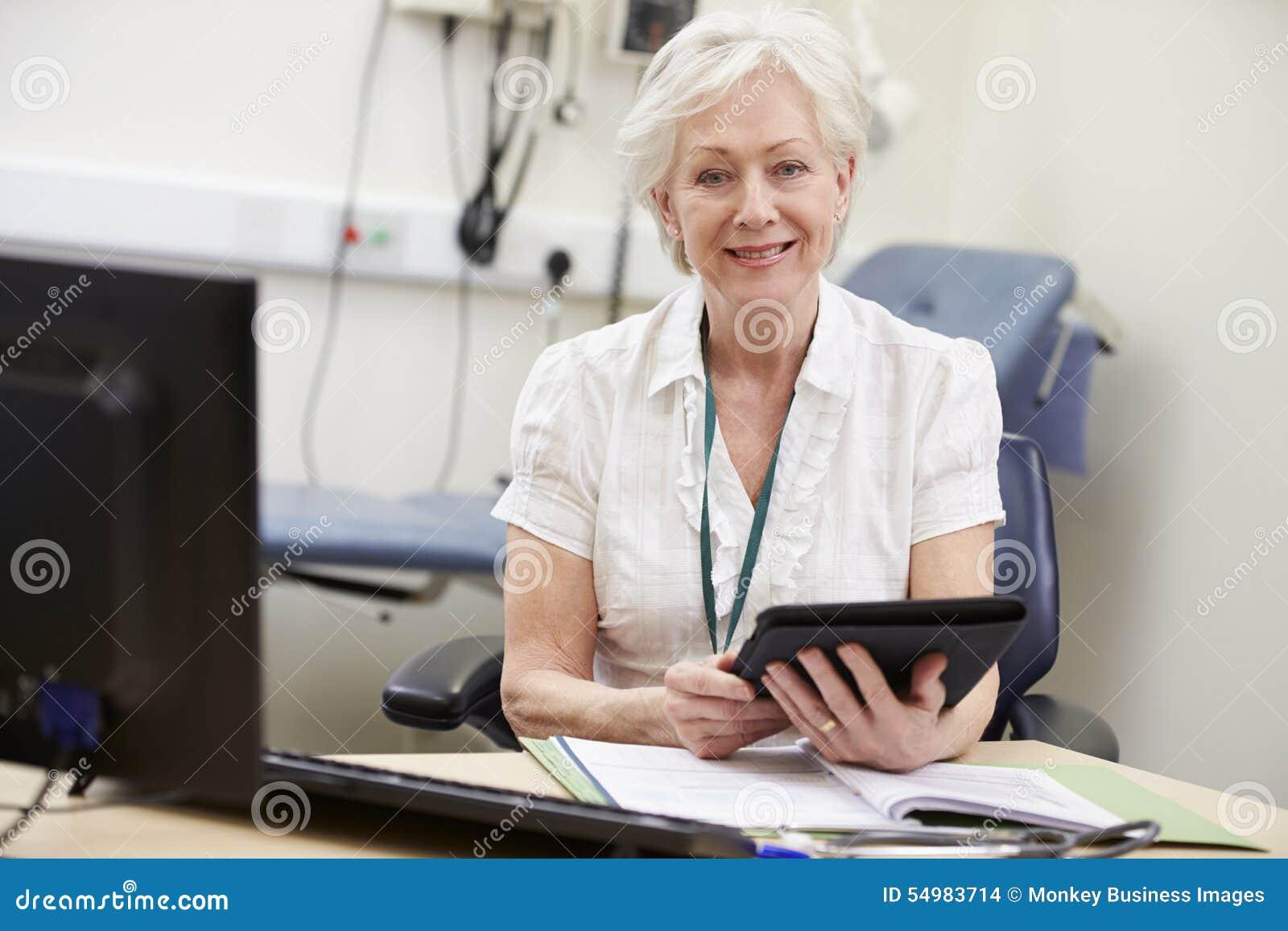 Kvinnlig konsulent Working At Desk som använder den Digital minnestavlan