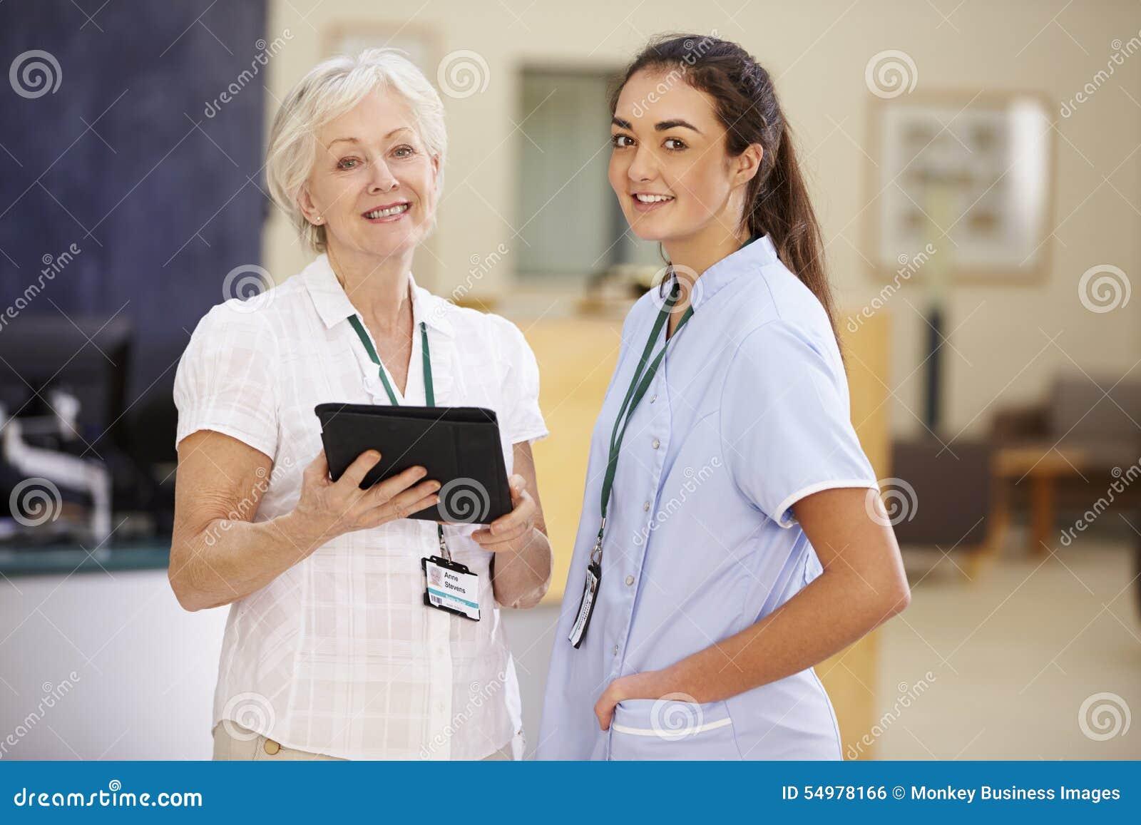 Kvinnlig konsulentIn Meeting With sjuksköterska Using Digital Tablet
