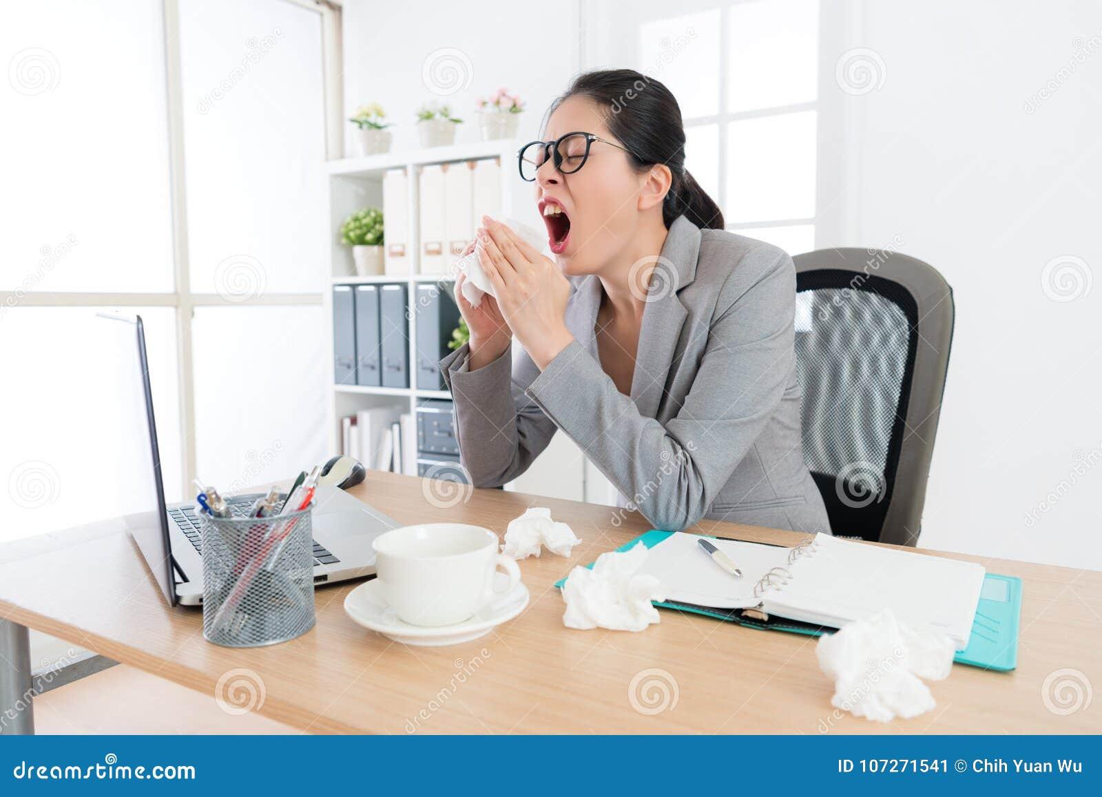 Kvinnlig kontorsarbetare som har näsallergiproblem