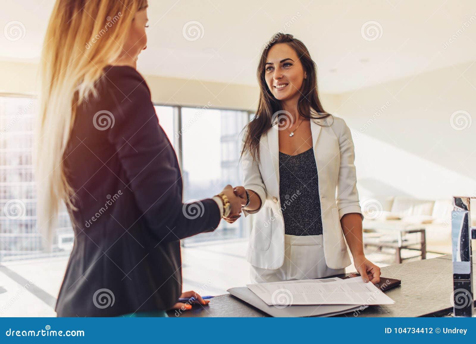 Kvinnlig kund som skakar händer med fastighetsmäklaren som instämmer för att underteckna ett avtalsanseende i ny modern studioläg