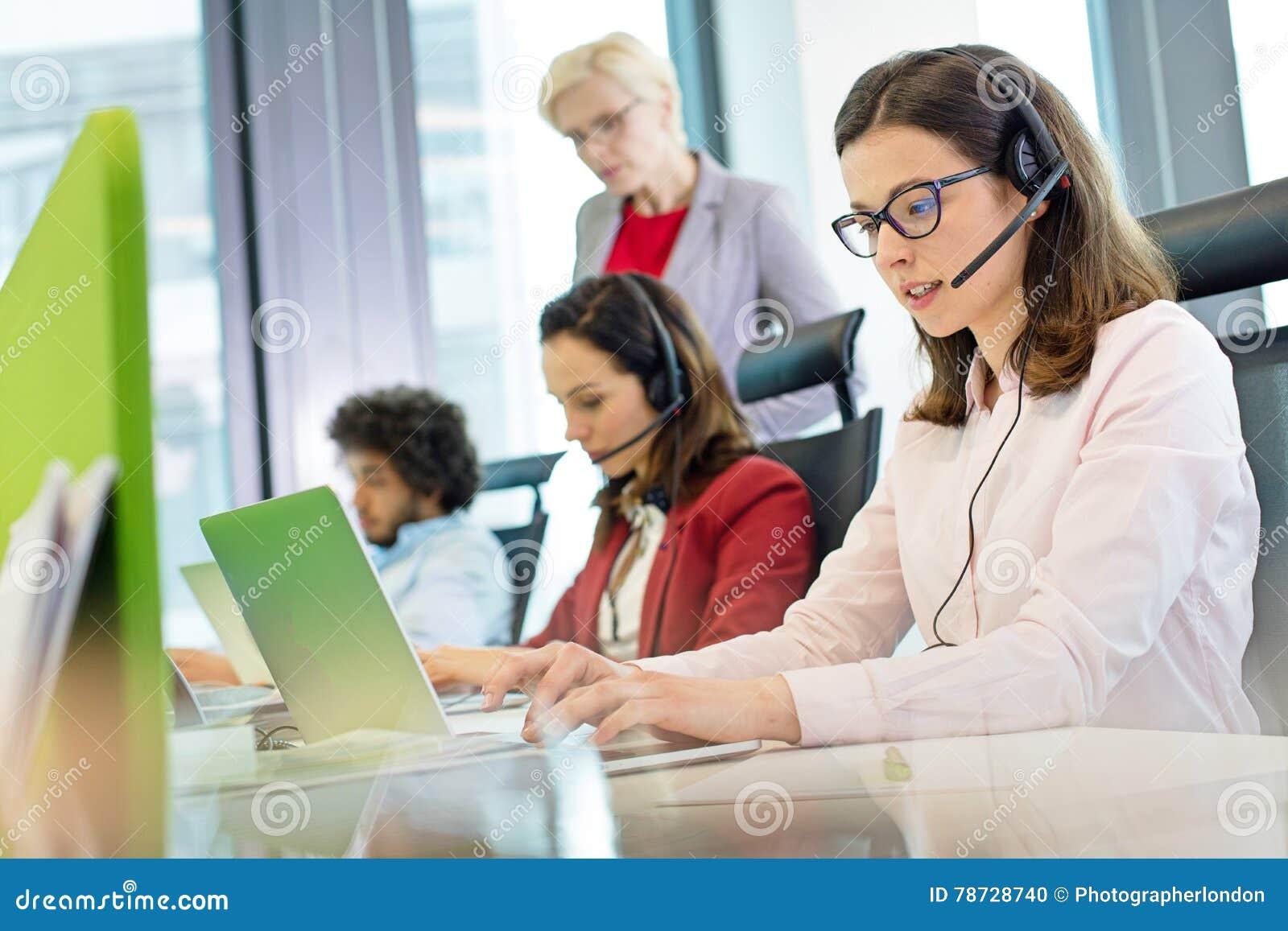 Kvinnlig kundtjänstrepresentant som använder bärbara datorn medan kollegor i bakgrund på kontoret