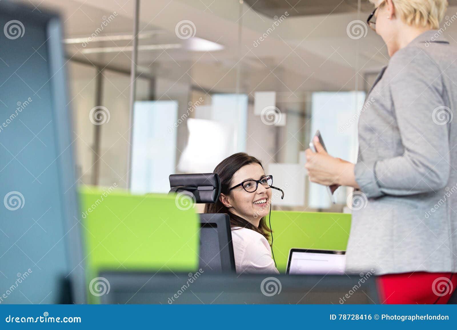 Kvinnlig kundtjänstrepresentant som i regeringsställning talar med chefen