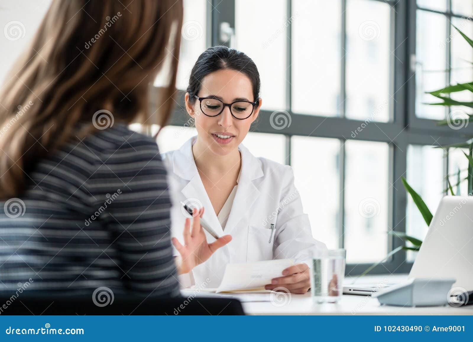Kvinnlig läkare som in lyssnar till hennes patient under konsultation