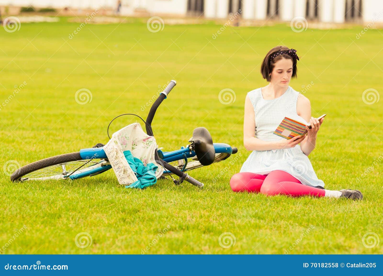 Kvinnlig läsning för ung hipster en bok utanför i parkera