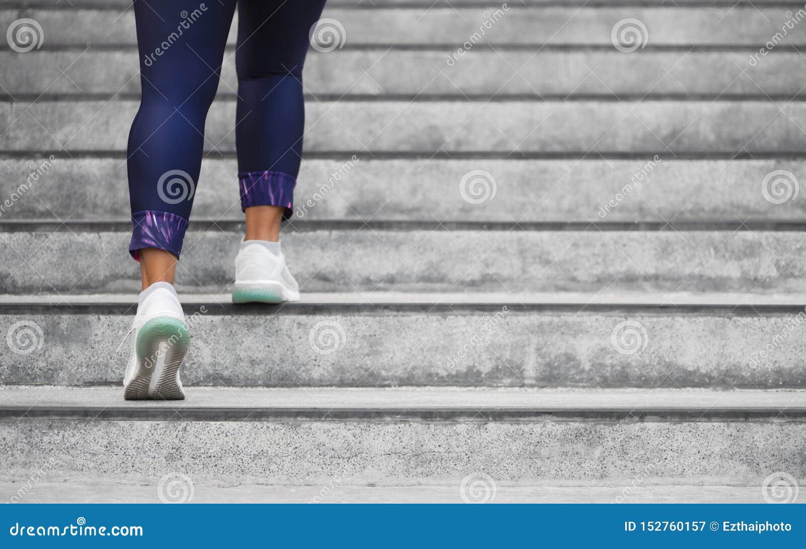 Kvinnlig löpareidrottsman nen som gör klättra för trappa Körande kvinna som gör körning upp moment på trappuppgång i stads- stad