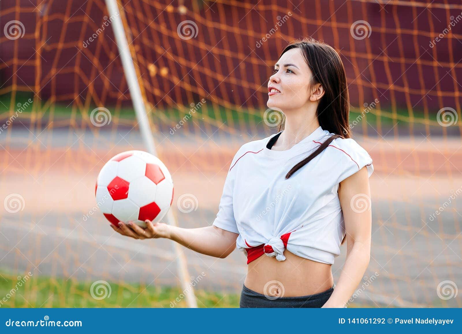 Kvinnlig målvaktboll i hans händer som står på fotbollmålet