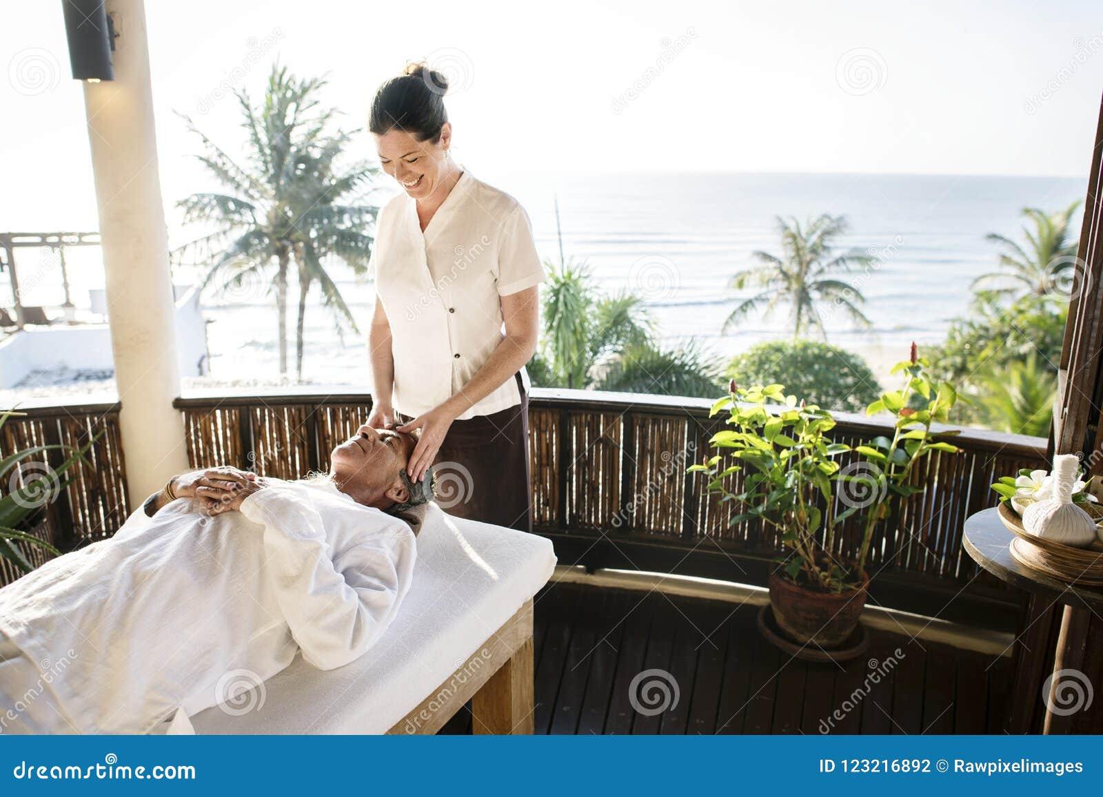 Kvinnlig massageterapeut som ger en massage på en brunnsort