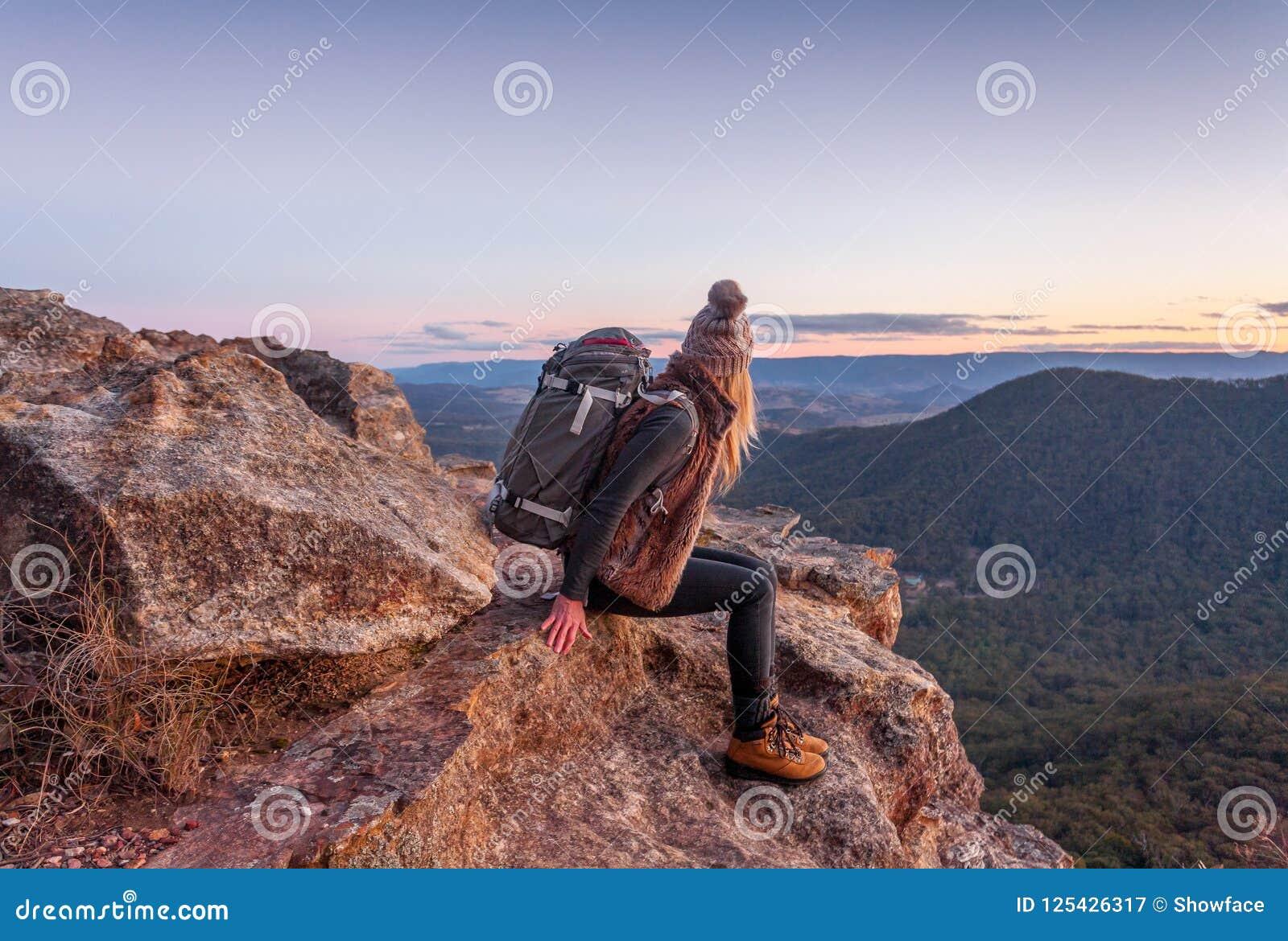 Kvinnlig med ryggsäcken på berg för blått för bergmaximum