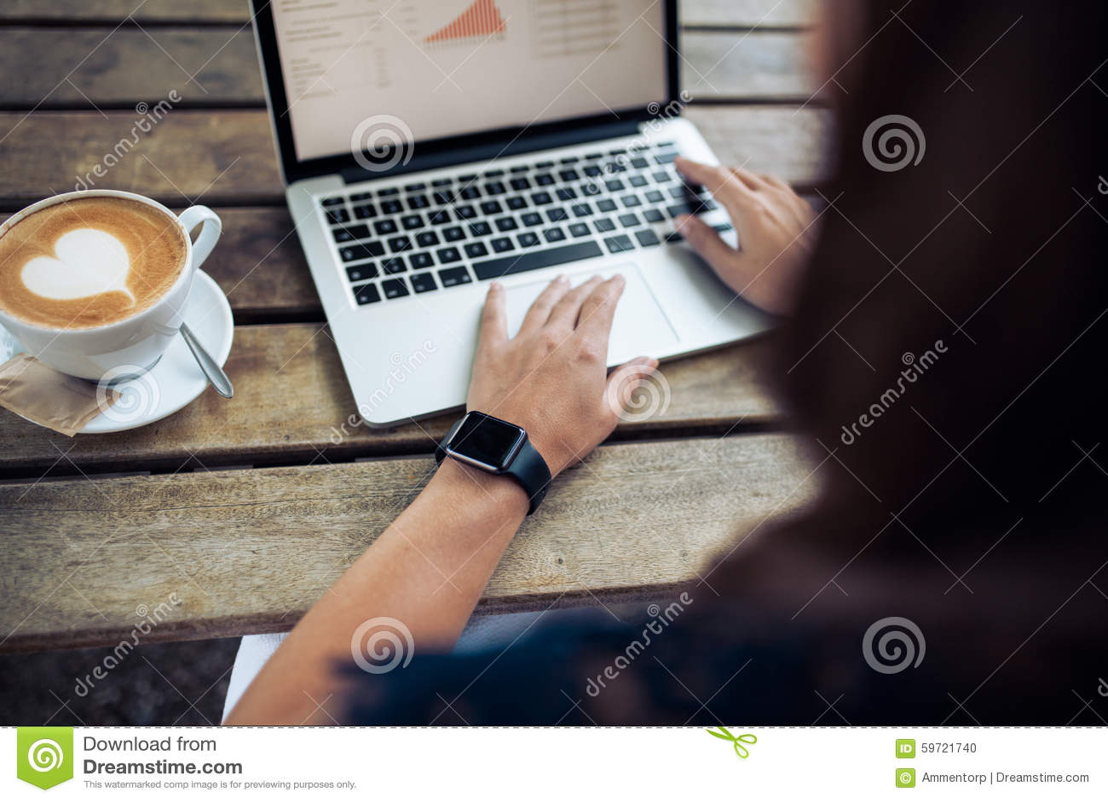 Kvinnlig med smartwatch genom att använda bärbara datorn på kafét