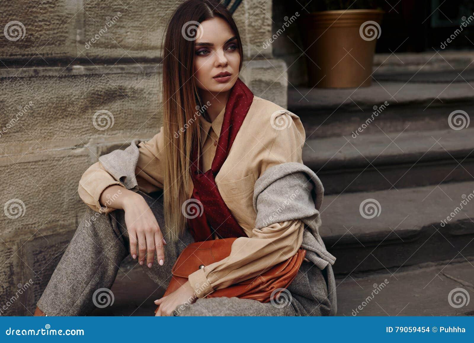 Kvinnlig modell In Fashionable Clothes som för mode poserar i gata