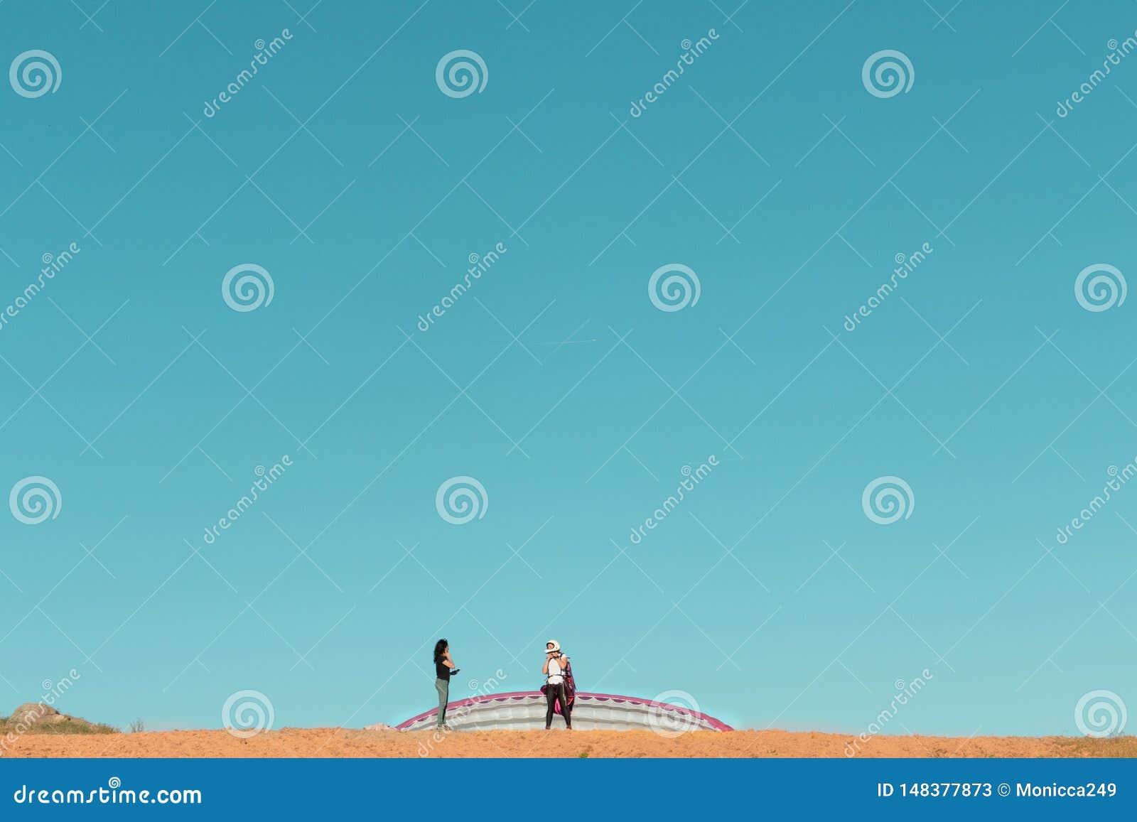 Kvinnlig paragliderpilot som förbereder sig att ta samtal av till en kvinna